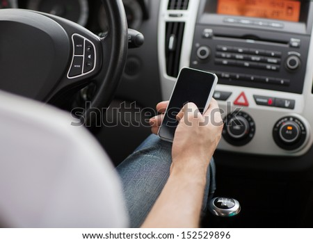 transportation and vehicle concept - man using phone while driving the car - stock photo