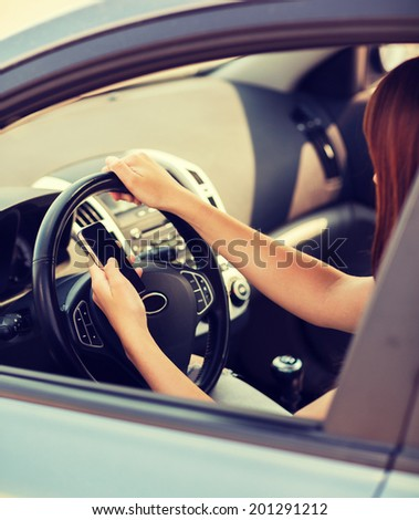 transportation and vehicle concept - woman using phone while driving the car - stock photo