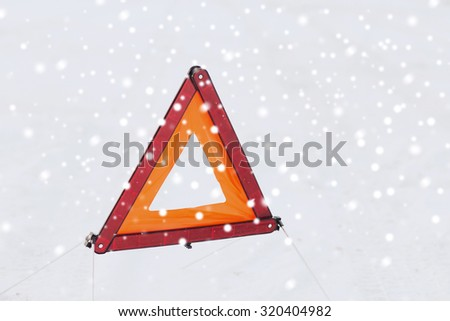transportation and winter concept - closeup of warning triangle on snow - stock photo