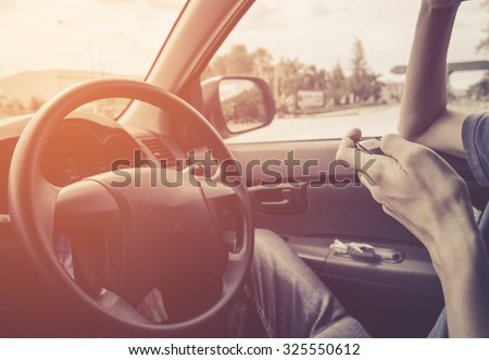 transportation concept , man play cellphone on drive in car - stock photo