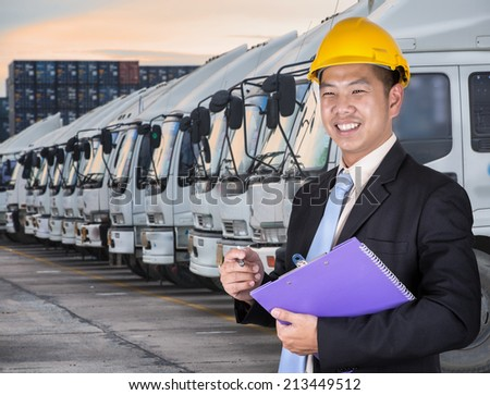 Transportation engineer with trucks of a transporting company in a row - stock photo