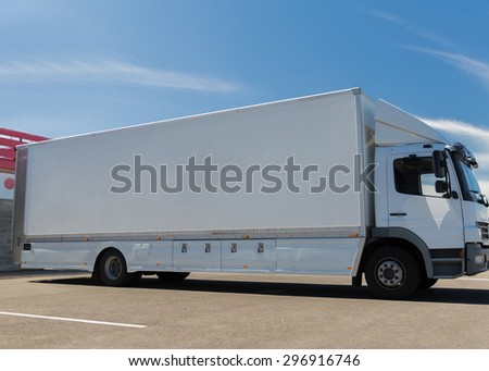transportation, freight transport and vehicle parts concept - white truck on city parking with copy space - stock photo