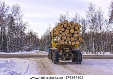 Transportation of logs on a truck on a forest road in winter - stock photo