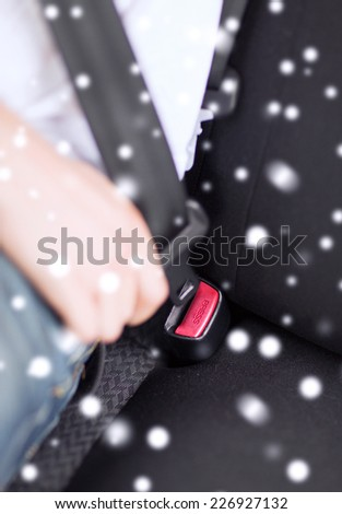 transportation, safety, people and vehicle concept - close up of man fastening seat belt in car - stock photo