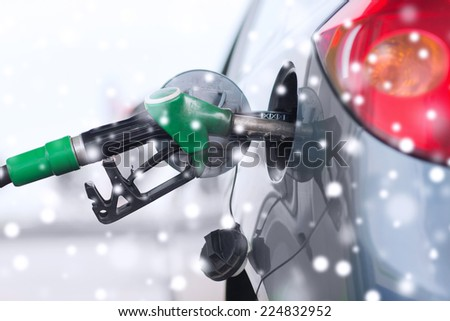 transportation, tanking and vehicle concept - close up of fuel hose nozzle in car tank - stock photo