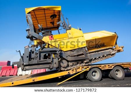 Transportation tracked paver machine during roadworks for asphalt paving - stock photo