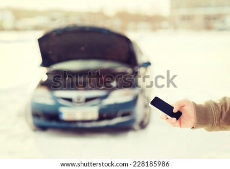 transportation, winter and vehicle concept - closeup of man with broken car and smartphone - stock photo