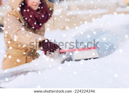 transportation, winter, weather, people and vehicle concept - closeup of woman cleaning snow from car windshield with brush - stock photo