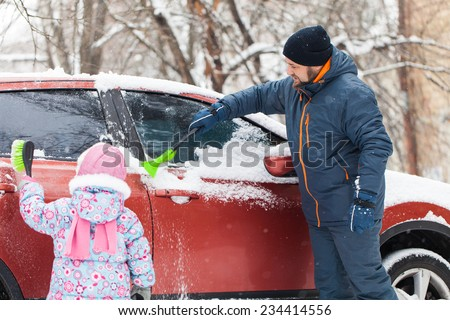 Transportation, winter, weather, people and vehicle concept - man and kid cleaning snow from car with brush - stock photo