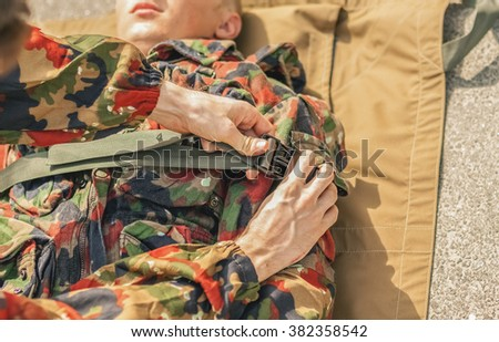 Transporting the wounded soldier. Fixation on a stretcher by belts - stock photo