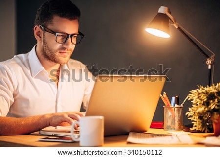 Trapped in office. Confident young man in eyewear working on his laptop while sitting at his working place at night time - stock photo