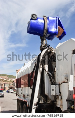 Trash bin in action being dump into the garbage truck. - stock photo