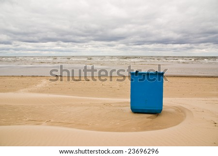 Trash box on the beach at the sea under cloudy sky - stock photo