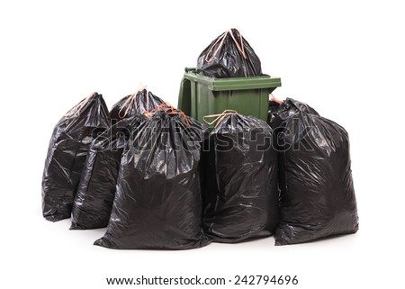 Trash can surrounded by a bunch of garbage bags isolated on white background - stock photo