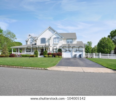 Trash Cans Blacktop Driveway Double Car Garage Large Two Story Suburban Neighborhood Home - stock photo