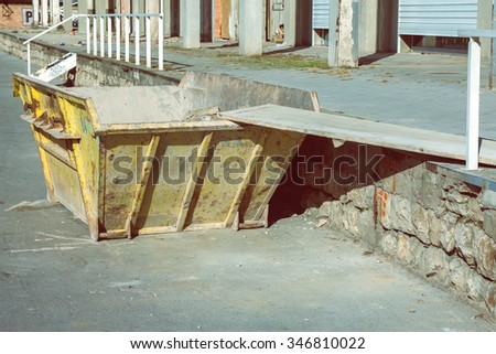 Trash container for concrete debris. Construction waste container. Made with shallow dof and vintage style. - stock photo
