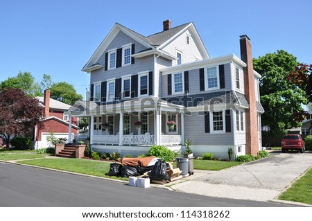 Trash Day on front yard lawn of Three story tall Suburban Home on sunny blue sky day residential neighborhood - stock photo