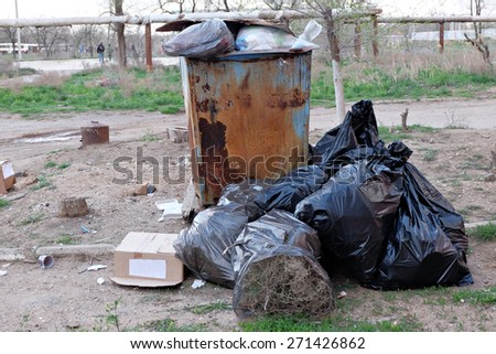 Trash dumpster and black packs of trash near in ghetto - stock photo