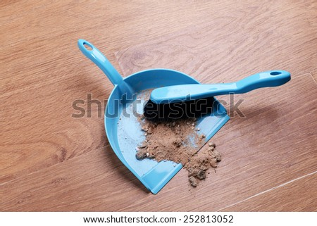 Trash in scoop on floor close-up - stock photo