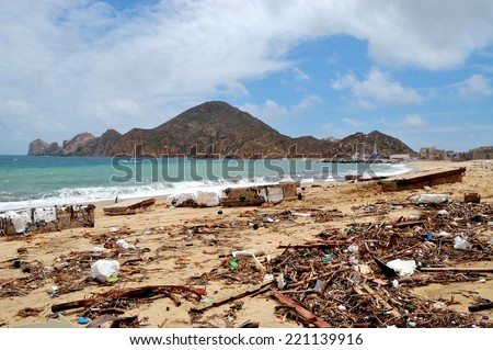 Trash on the Medano beach Cabo San Lucas and view of mountains - stock photo