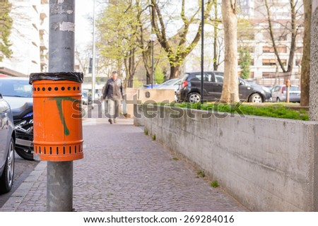 Trash orange metal for the collection of waste of the road - stock photo