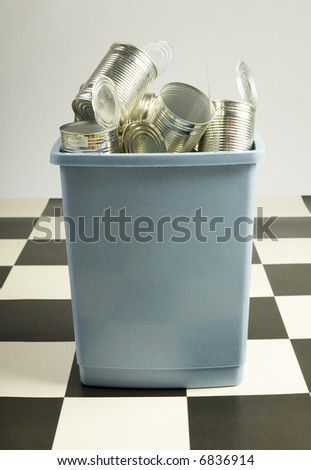 Trashcan filled with tins standing on floor. Front view - stock photo