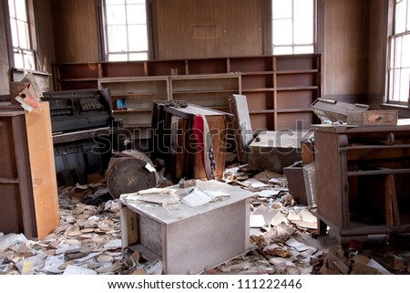 Trashed room with old furniture and papers scattered about. - stock photo
