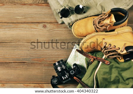 Travel accessories set on wooden background: old hiking leather boots, pants, backpack, map, vintage film camera and sunglasses. Top view point.