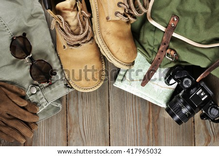 Travel accessories set on wooden background: old hiking leather boots, pants, backpack, map, gloves, vintage film camera and sunglasses. Top view point. - stock photo
