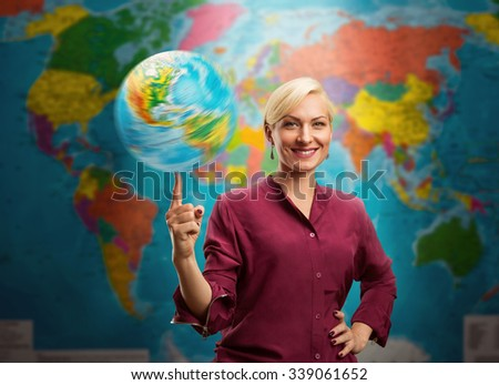 Travel agent woman with a globe against a map of the world - stock photo