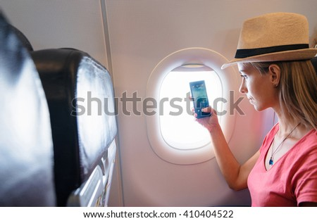 Travel and technology. Young woman in plane taking photo on her smartphone while sitting in airplane seat. Focus on phone. - stock photo