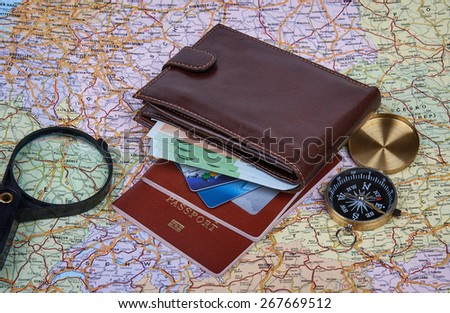 Travel arrangement of wallet with euro, credit card two passports, compass and magnifying glass on a map background. Travel concept.