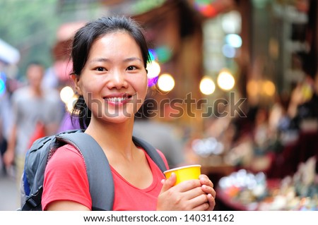 travel asian woman with a cup of coffee smile at street - stock photo