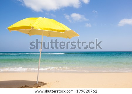 travel background with a yellow sunshade, blue sky, turquoise sea and a beautiful beach, Fuerteventura, Canary Islands, Spain, Europe - stock photo