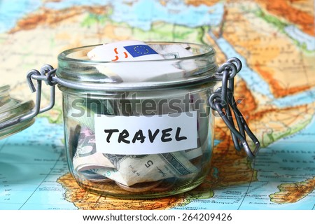 Travel budget - vacation money savings in a glass jar on world map - stock photo