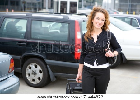 Travel: Cheerful Woman Traveler in Parking Lot At Airport - stock photo