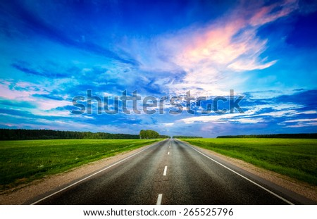 Travel concept background - road and stormy dramatic sky on sunset - stock photo