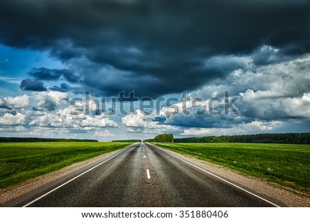 Travel concept background - road and stormy sky - stock photo