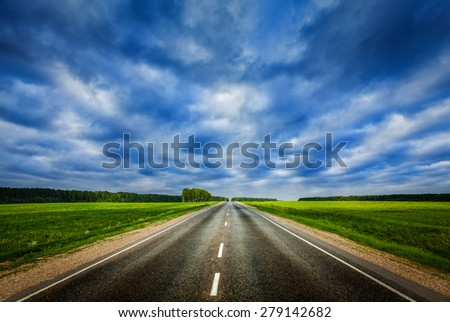 Travel concept background - road under dramatic stormy cloudy sky - stock photo