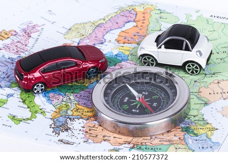 Travel concept, compass and small, toy car map, isolated on white background. - stock photo