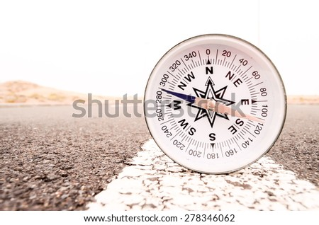 Travel Concept Compass on the Asphlat Road - stock photo