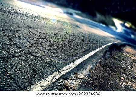 Travel concept. Cracked asphalt and curve road.Road lines - stock photo