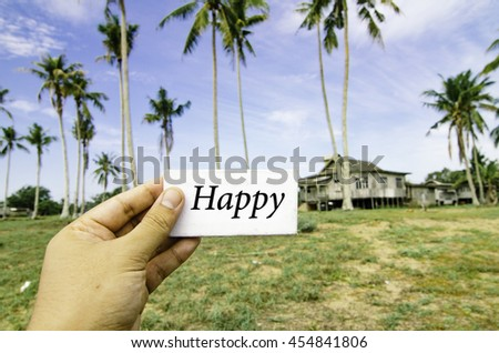 travel concept, cropped hand holding white canvas with word happy over blurred background of rural area.wooden house surrounded by coconut tree at sunny day and cloudy blue sky - stock photo