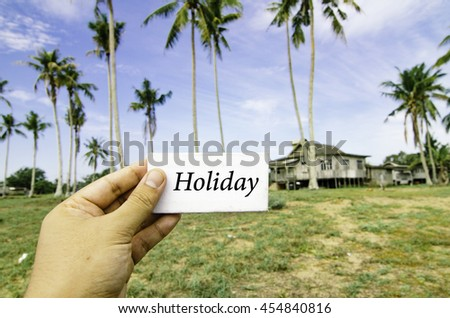 travel concept, cropped hand holding white canvas with word holiday over blurred background of rural area.wooden house surrounded by coconut tree at sunny day and cloudy blue sky - stock photo