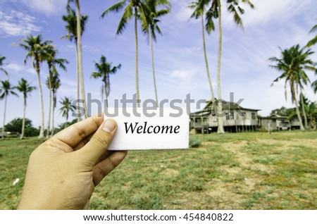 travel concept, cropped hand holding white canvas with word welcome time over blurred background of rural area.wooden house surrounded by coconut tree at sunny day and cloudy blue sky - stock photo