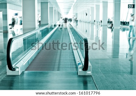 Travel concept. Escalator inside modern airport terminal. Image in blue colors with blur - stock photo