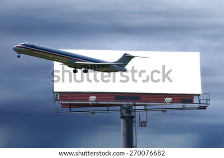 Travel concept showing a plane flying out of a billboard against a stormy background. Easily add your vacation/travel image to white billboard.