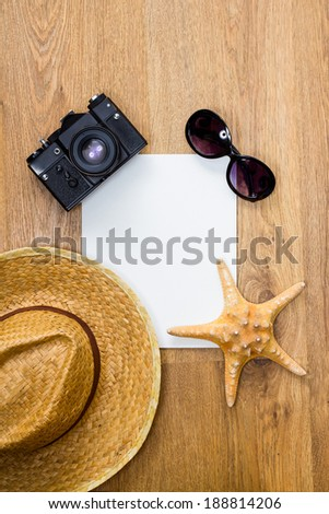 Travel concept. Top view of vintage camera, braided hat, starfish, pair of glasses and blank white paper on a wooden background.  - stock photo