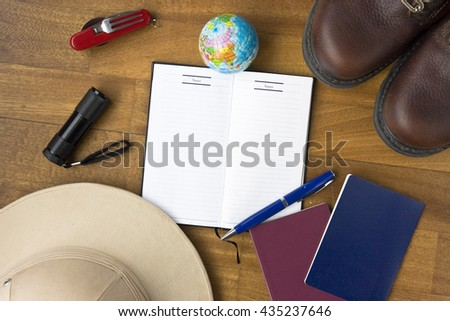 Travel concept - tourist accessories with an empty notebook with space for design, on wooden background