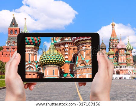 travel concept - tourist photographs picture of Pokrovsky Cathedral on Vasilevsky Descent of Red Square in Moscow Kremlin on tablet pc - stock photo